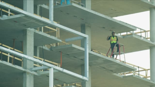 high rise newly constructed city building being developed - sicurezza sul posto di lavoro video stock e b–roll