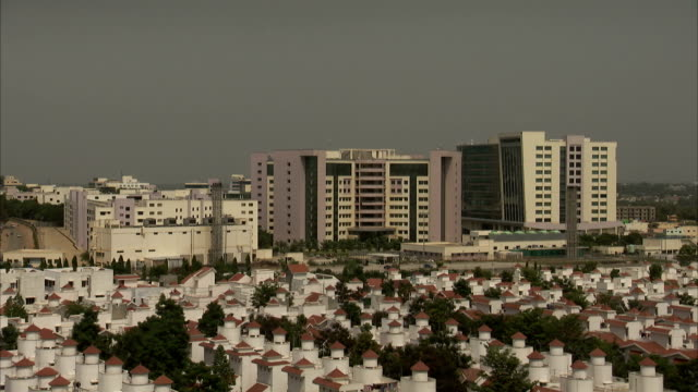 high rises sit behind red-roofed homes in bangalore, india. - bangalore stock videos and b-roll footage