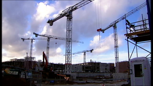 vídeos de stock, filmes e b-roll de 'high risk activity' revealed at alder hey children's hospital traffic along past hospital buildings cranes on construction site 'nhs' sign on crane... - moving activity