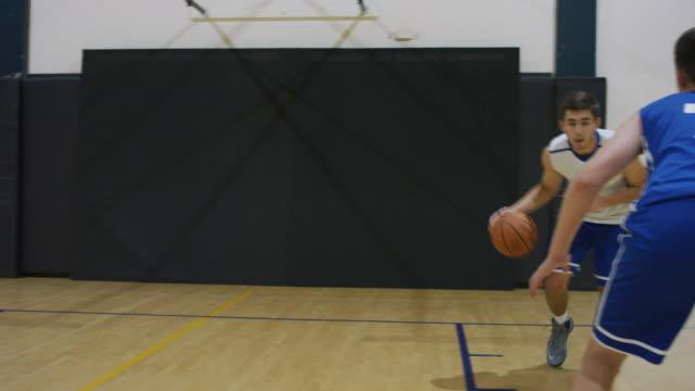Middelbare school atleet dribbelt basketbal van Hof