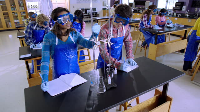 high school chemistry lab partners measure the meniscus in a burette and take notes. - chemistry点の映像素材/bロール