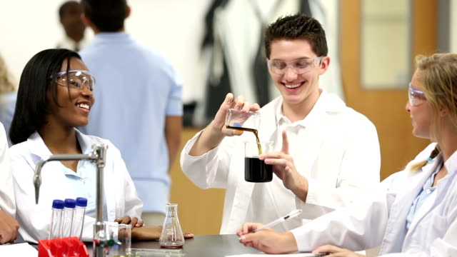 High school chemistry student leading science group experiment