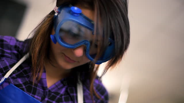 A high school chemistry student wearing safety goggles take notes.