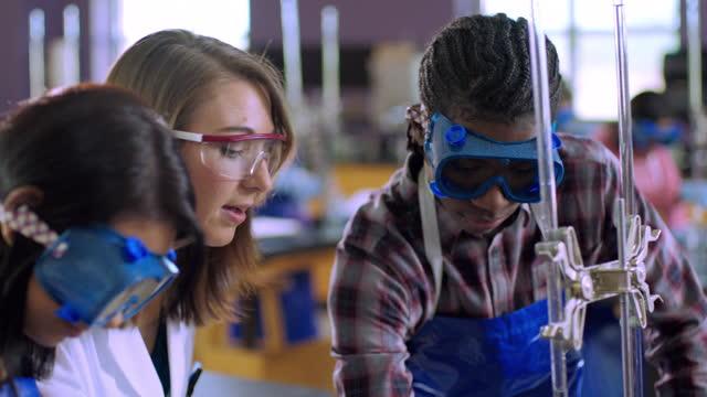 A high school chemistry teacher talks a student through an experiment.