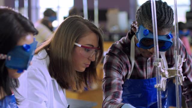 vídeos y material grabado en eventos de stock de a high school chemistry teacher talks through observations with two students. - gafas panoramicas