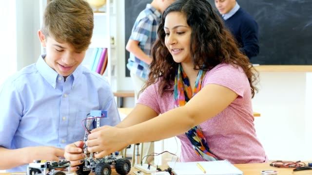 vídeos de stock, filmes e b-roll de colegas de escola montam veículos robóticos em classe de tecnologia - meninos adolescentes