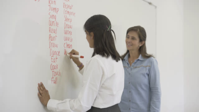vídeos de stock e filmes b-roll de high school female students writing english verbs on the whiteboard - sala de aula