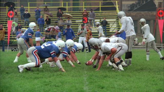 ws pan high school football teams playing on field - gymnasium bildbanksvideor och videomaterial från bakom kulisserna