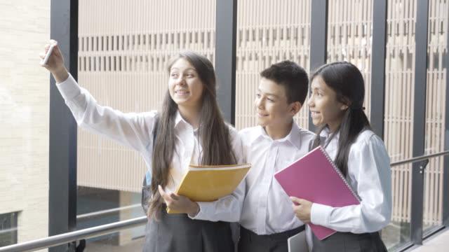 vídeos y material grabado en eventos de stock de amigos de la high school secundaria tomando un selfie en la escuela - pasillo de entrada