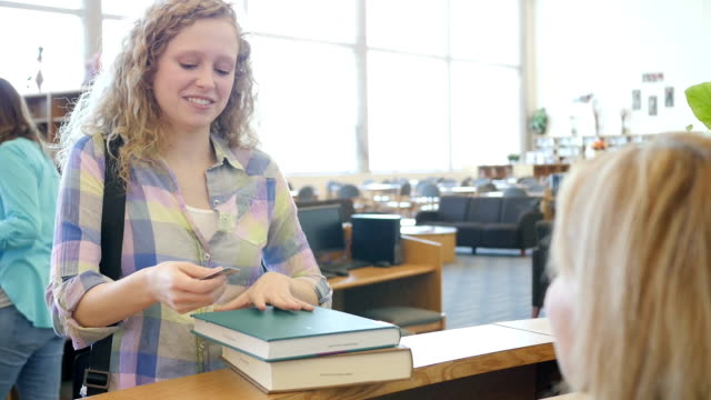 high school girl checking out books at library checkout counter with library id card - librarian stock videos & royalty-free footage