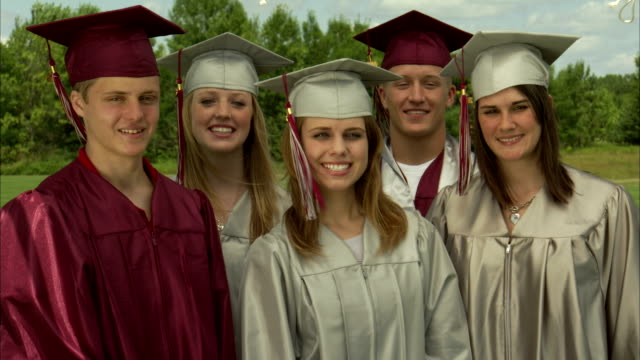 MS High school graduates show diplomas to camera and smile / Appleton, Wisconsin, USA