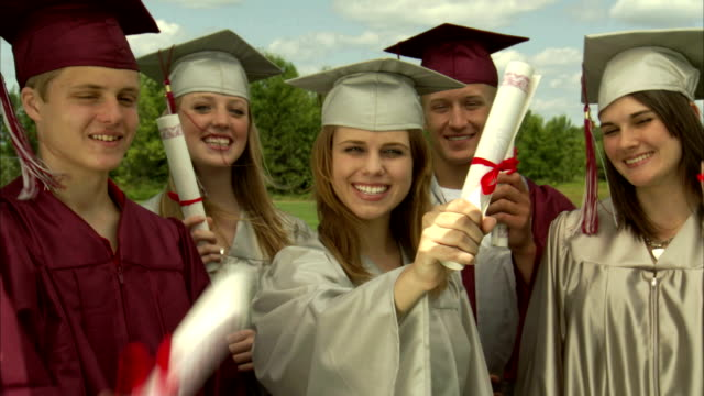 MS High school graduates showing diplomas to camera / Appleton, Wisconsin, USA