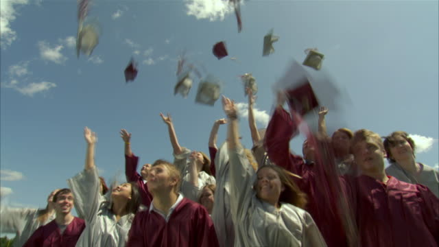 ws slo mo high school graduates (17-19) throwing caps in air and giving high fives / appleton, wisconsin, usa - 投げる点の映像素材/bロール