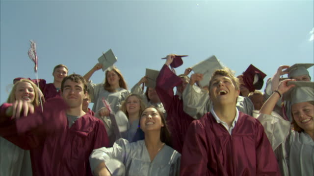 stockvideo's en b-roll-footage met ms tu slo mo high school graduates (17-19) throwing caps in air / appleton, wisconsin, usa - hoed
