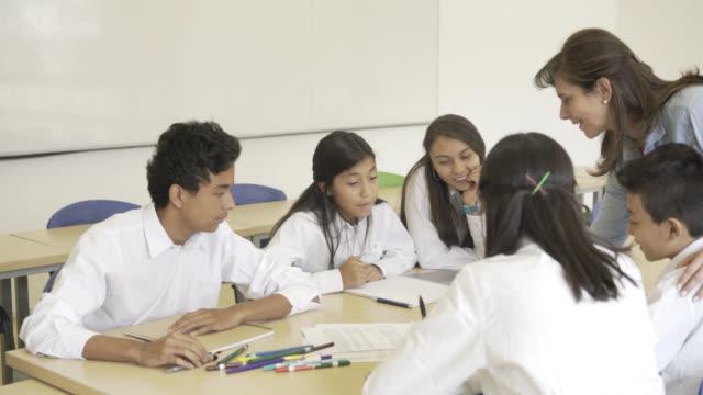 vídeos y material grabado en eventos de stock de niños de secundaria en clase escuchando al profesor - uniforme