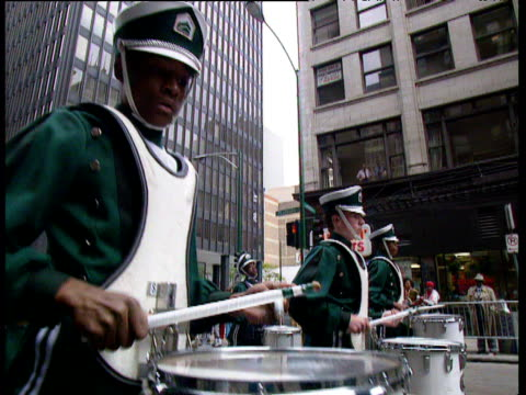 High school marching band dance their way through streets of Chicago playing drums trombones etc; Chicago