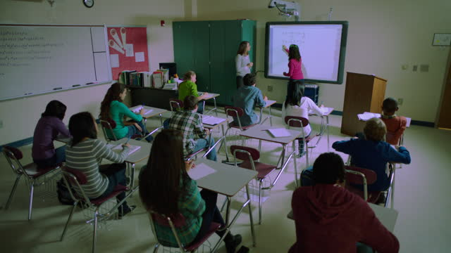 a high school math teacher uses a smart board to demonstrate equations during class. - interactive whiteboard stock videos & royalty-free footage