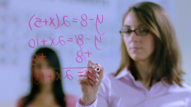 Teacher writing equation across lens, female student observes behind her