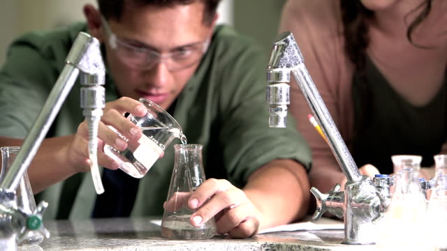 High school student in chemistry class pouring liquid