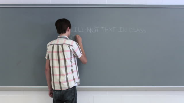 High school student writing lines on blackboard
