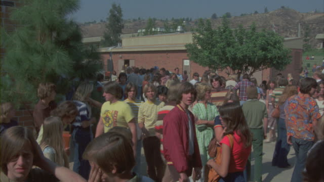 High school students crowd a school campus.