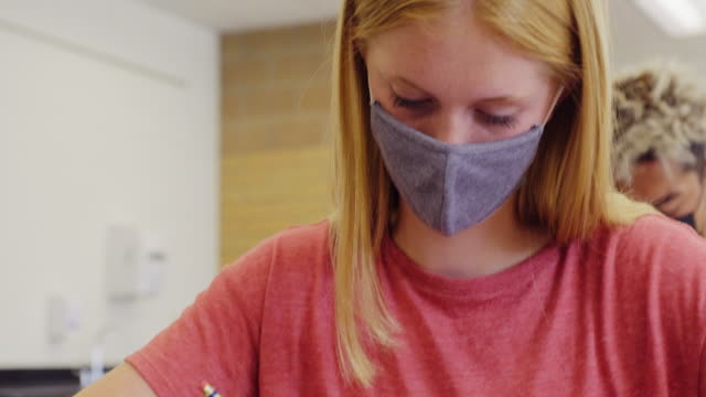 high school students in classroom wearing protective face mask - educational exam stock videos & royalty-free footage
