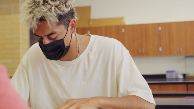vídeos y material grabado en eventos de stock de estudiantes de secundaria en el aula usando máscara protectora para la cara - sólo grupo de adolescentes