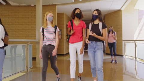 gymnasieelever i skolan bär skyddande ansiktsmask - skolbyggnad bildbanksvideor och videomaterial från bakom kulisserna