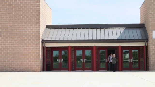 vídeos de stock e filmes b-roll de high school students leaving school - escola secundária educação