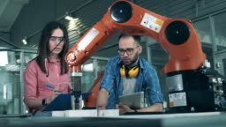High school students studying robotics technologies at university lab. Two engineers are looking at a robot-like device in motion