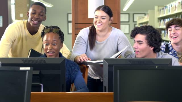 vidéos et rushes de des élèves du secondaire travaillent ensemble sur des ordinateurs de bibliothèque - 14 15 years