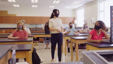 vídeos y material grabado en eventos de stock de profesor de escuela secundaria y estudiantes en el aula con máscara protectora para la cara - maestro