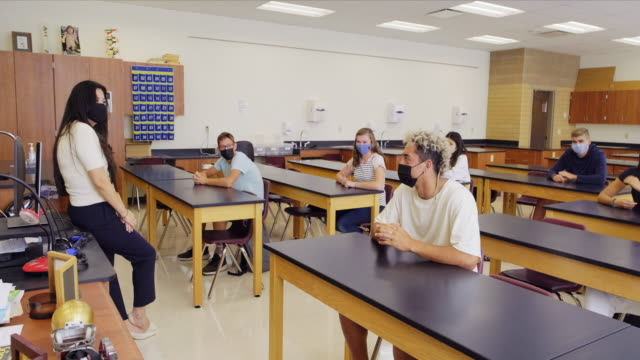 vídeos de stock e filmes b-roll de high school teacher and students in classroom wearing protective face mask - educação