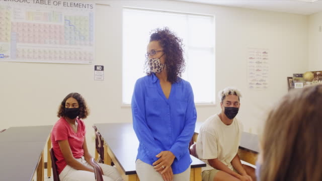 high school teacher and students in classroom wearing protective face mask - secondary school child stock videos & royalty-free footage