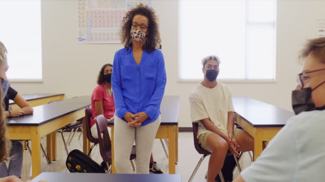 vidéos et rushes de enseignant d'école secondaire et étudiants dans la salle de classe portant le masque protecteur de visage - élève du secondaire