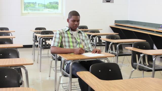 vidéos et rushes de high school teacher collecting assignment from student - cartable