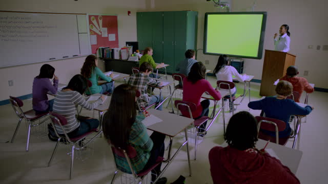 a high school teacher gives a lecture from her podium to a diverse class. - interactive whiteboard stock videos & royalty-free footage
