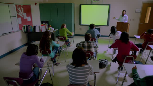 a high school teacher gives a lecture to a diverse class of students. - projection screen stock videos & royalty-free footage