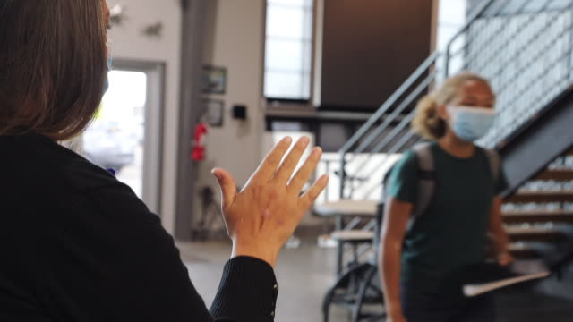high school teacher welcoming students with general greeting and hand wave all wearing face masks in classroom setting 4k video - female high school student stock videos & royalty-free footage