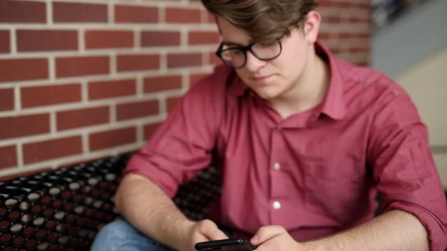 high school teenager looking at cellphone - リーハイ点の映像素材/bロール