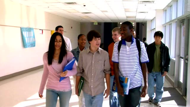 High schools students pass each other in the hallway as they go to class.
