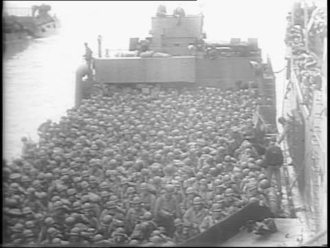 high shot french beachhead busy with supply activity / soldiers make landfall in boat / soldiers carry supplies from boat onto shore / cranes and... - normandy stock videos & royalty-free footage
