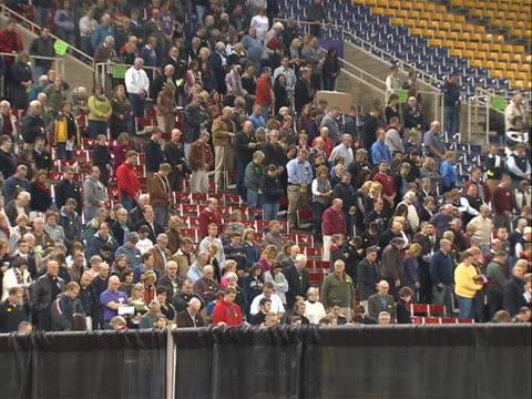 vídeos y material grabado en eventos de stock de high shot of crowds of ia voters in stands / bleacher seats of gymnasium - voters wearing bright yellow round stickers - asiento