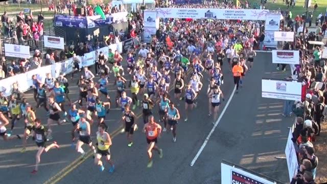 vídeos de stock, filmes e b-roll de high shot of thousands of runners starting the cherry blossom ten mile run in washington dc - salmini