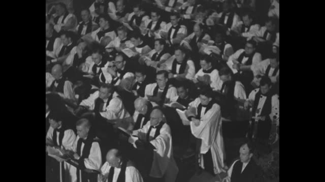 procession of clergy in the cathedral of saint john the divine / high shot: new bishop horace donegan walks down center aisle with open book along... - 羊飼いの棒点の映像素材/bロール