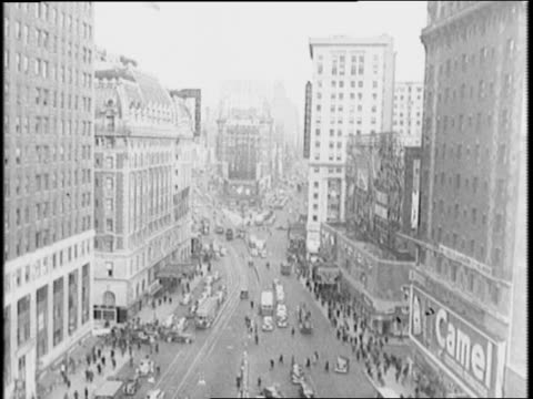 High shot Times Square with cars pedestrians and Camel cigarette ad / emergency workers usher people into buildings and clear streets of cars /...