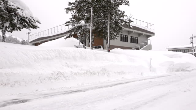 high snow banks line side of road in town hit by huge snowfalls - 深い雪点の映像素材/bロール