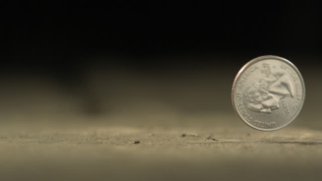 high speed american quarter dollar falls on to surface and bounces away - ジョージ・ワシントン点の映像素材/bロール