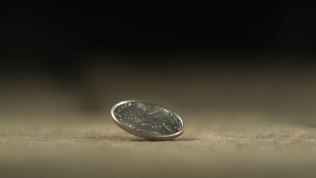 vídeos de stock, filmes e b-roll de high speed american quarter dollar spins and falls on to surface - moeda