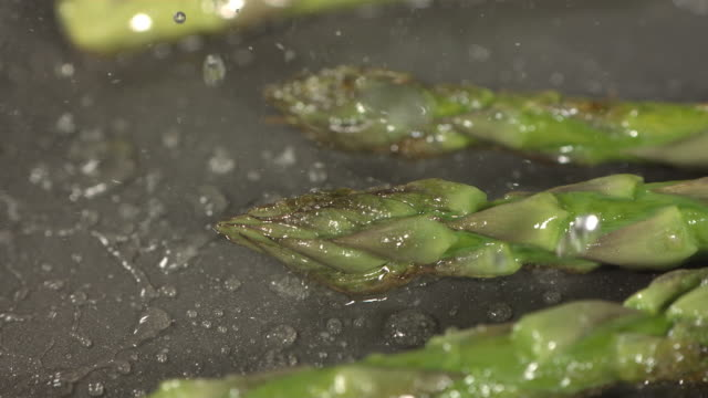 High speed asparagus tips cooking in frying pan